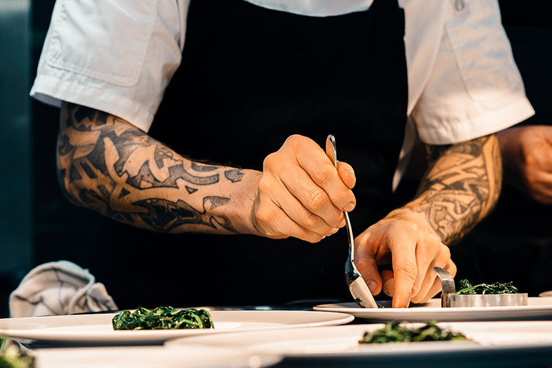 A chef plating dishes with food.