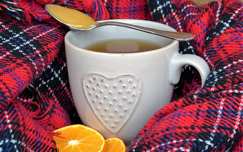 Tea with a spoonful of honey and orange slices