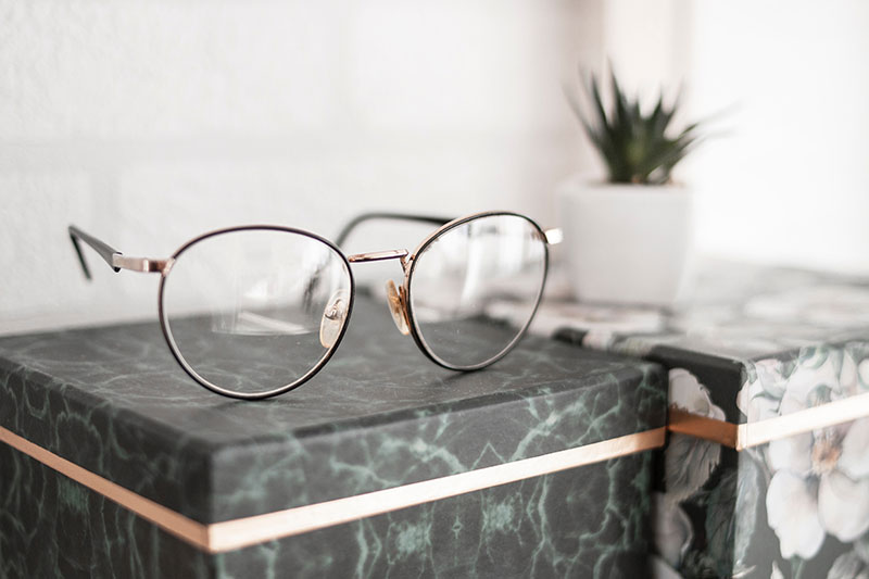 A pair of reading glasses resting on a table